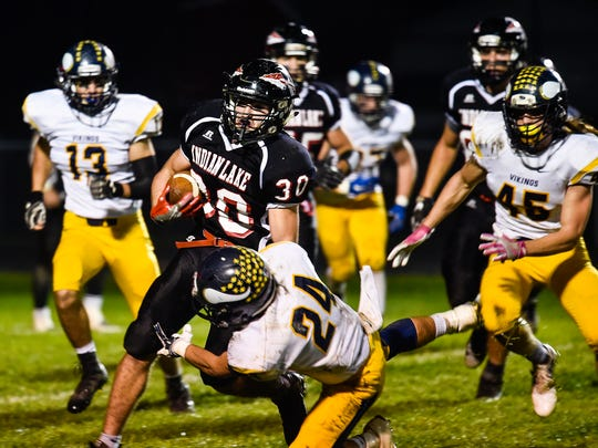 Indian Lake's Andrew Hulbert runs the ball before being stopped by River Valley's Evan Bandyberry during the River Valley at Indian Lake regional quarterfinal game this season. Friday night high school football is important in Ohio, but the Big Ten does not hold it sacred as it will begin televising Friday night games.
