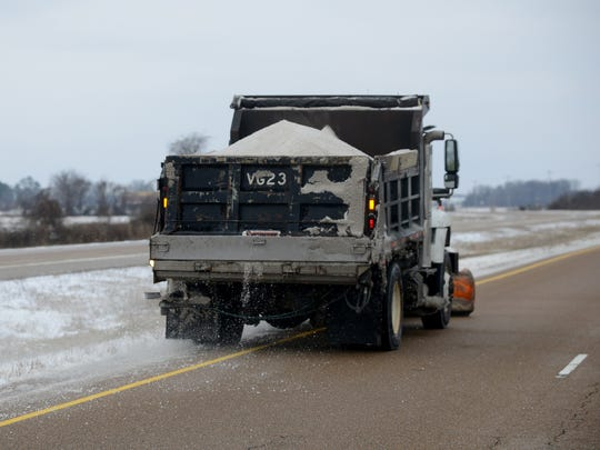 A Tennessee Department of Transportation truck clears snow and ice from HWY 223 while spreading a salt mix in West Madison County, Friday afternoon.