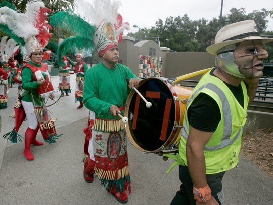 Members of Los Matachines de Michoacan march down the sidewalk leading into Libbey Bowl in Ojai as they perform at the 50th annual Ojai Valley Mexican Fiesta.