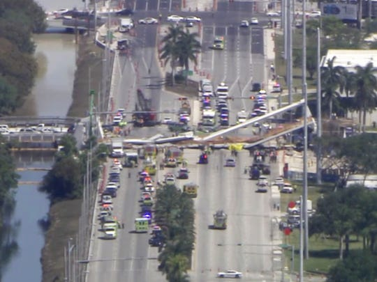 In this frame from video, emergency personnel work at the scene of a collapsed bridge in the Miami area, Thursday, March 15, 2018.