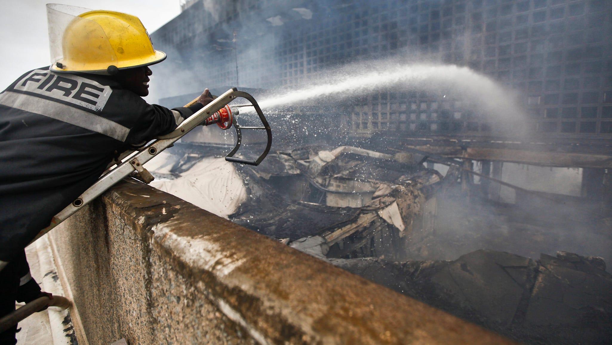 A firefighter waters smoldering debris.
