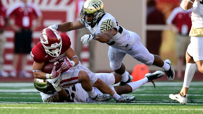 Indiana Hoosiers wide receiver Mitchell Paige (87) is tackled by Wake Forest Demon Deacons defensive back Brad Watson (25) and defensive back Ryan Janvion (22) during the second half of the game at Memorial Stadium. Wake Forest defeated Indiana 33-28.