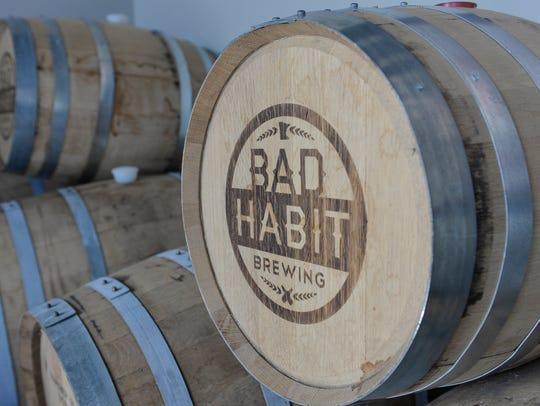 A barrel bears the logo of Bad Habit Brewing Co. in