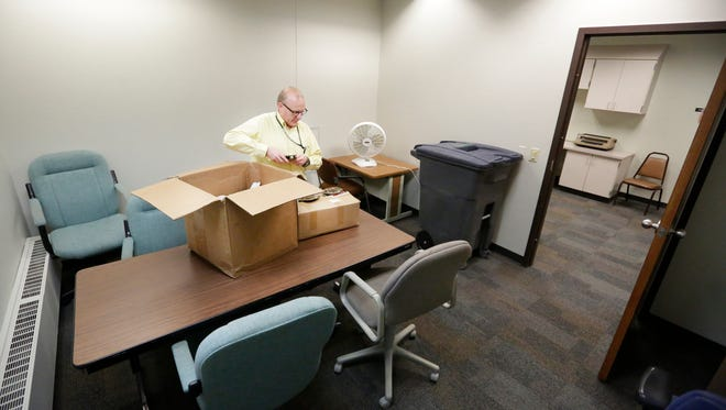 Space is tight at the Veteran's Service Office in Fond du Lac. Rick Patton of the service unpacks veteran grave markers Thursday in a square room used for group meetings of as many as 10 people.