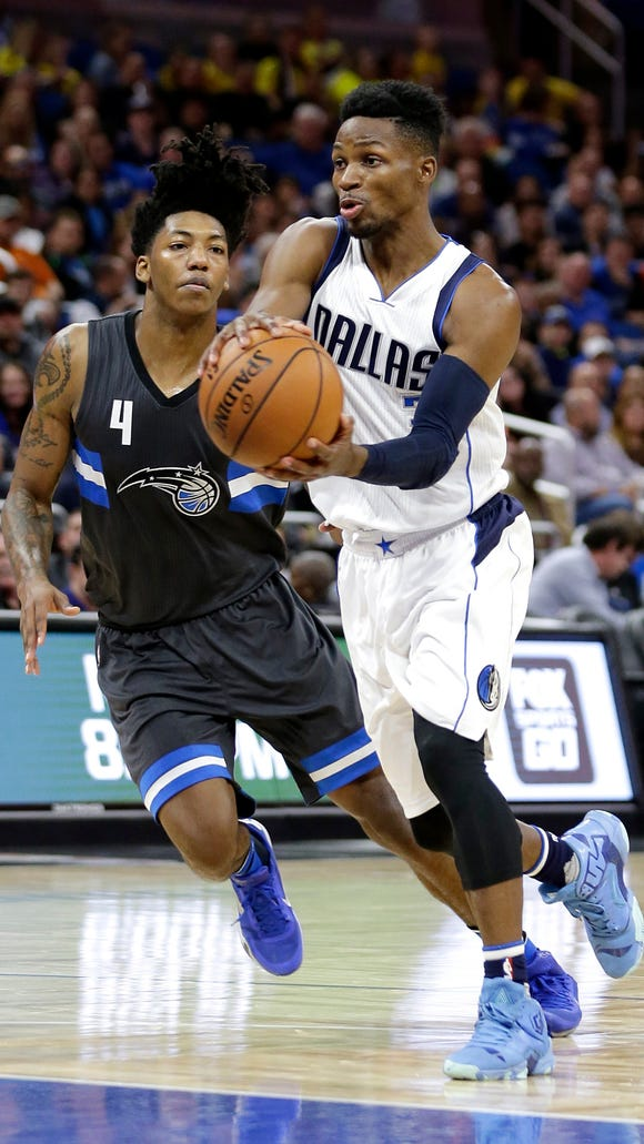 Dallas Mavericks' Jonathan Gibson, right, passes the ball as he gets past Orlando Magic's Elfrid Payton (4) during the first half of an NBA basketball game, Saturday, Nov. 19, 2016, in Orlando, Fla. (AP Photo/John Raoux)