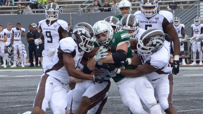 Western Michigan defenders swarm Eastern Michigan running back Ian Eriksen on Saturday at Rynearson Stadium in Ypsilanti.