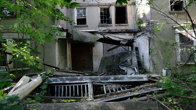 The porch is in ruins at the abandoned and boarded-up mansion in Burlington City built for industrialist Andrew McNeal.