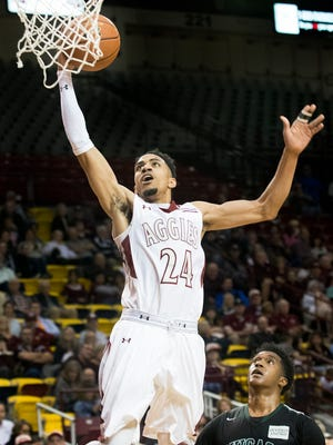 New Mexico State junior guard Matt Taylor goes up for the dunk against Chicago State's Delundre Dixon during second half action Saturday night at the Pan American Center.