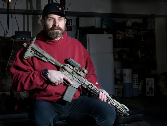 Dana McLendon, a Second Amendment advocate, poses with his AR-15 rifle in his garage of his Franklin home on Wednesday, March 14, 2018.