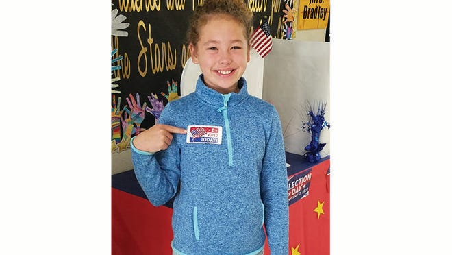 Third grader Parker Freeman proudly wears her voting sticker.
