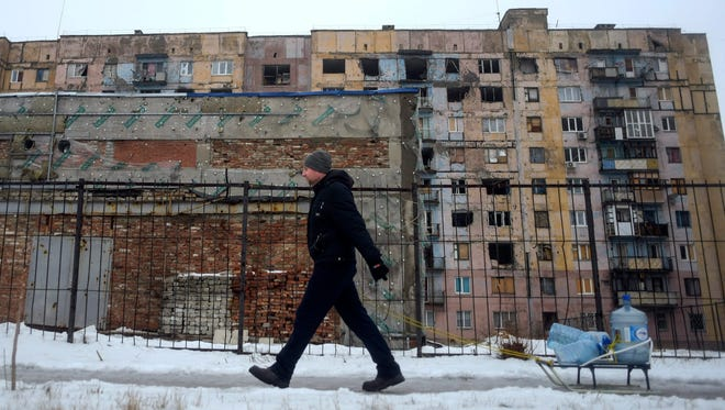 A man drags a sled with empty bottles for water in front of a building  damaged from shelling in Avdiivka, Ukraine, on Feb. 5, 2017.