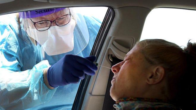 Claudia Moore adminsiters a coronavirus test to Brenda McCartney at Kintegra Health's drive through mobile testing site at St. John's Missionary Baptist Church in Gastonia earlier this summer.