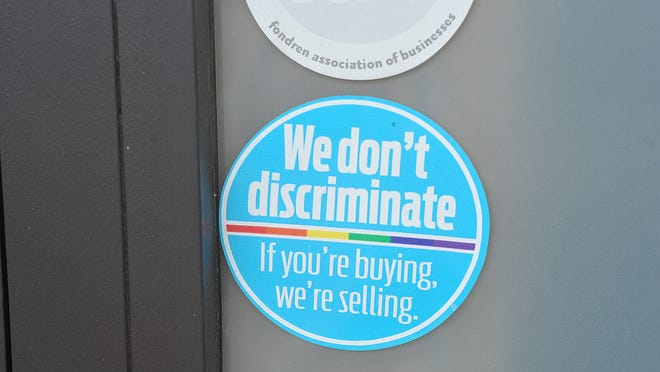 Anti-discrimination stickers are posted on the front door of William Wallace Salon in Fondren.