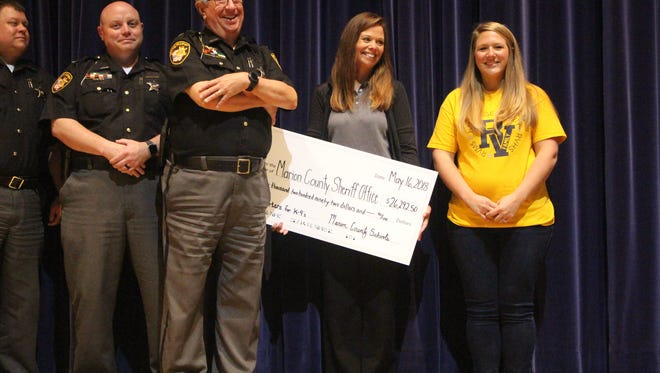 Sheriff Tim Bailey, center, stands next to a check for $26,292.50 that was presented to his office by members of River Valley Local Schools on Wednesday. Four school districts spent the past two months raising money for a new K-9 deputy.