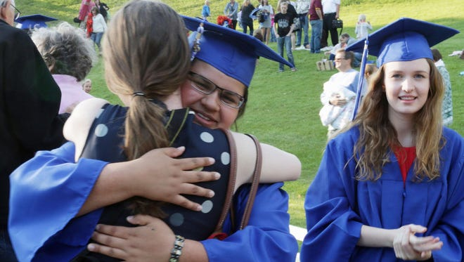 Kohler High School graduate Sierra Aguirre shares an embrace as classmate Emily Boland looks on Wednesday, June 3, during Kohler's annual Scroll Night at Ravine Park.