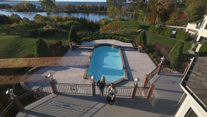 Holly Creek, left, Holly Creek Homes, and Donna Snyder, with Nothnagle Realtors, take in the view from the first floor balcony that overlooks the pool, Irondequoit Bay, and Lake Ontario, at the property at 407 Sundance Trail. The pair are co-listing the house.
