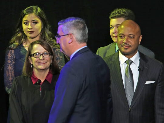 Eric Holcomb takes the stage as Chief Justice Loretta Rush, left, and Curtis Hill, right, smile, at the Indiana Gubernatorial Inauguration ceremony held at the Indiana State Fairgrounds, Monday, January 9, 2017.
