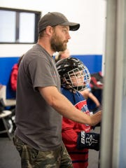 Todd Porter and his son, Peter Chau, 8, of Jackson wait for Peter's turn on the ice at Howell Ice Arena on Aug. 3, 2017.
