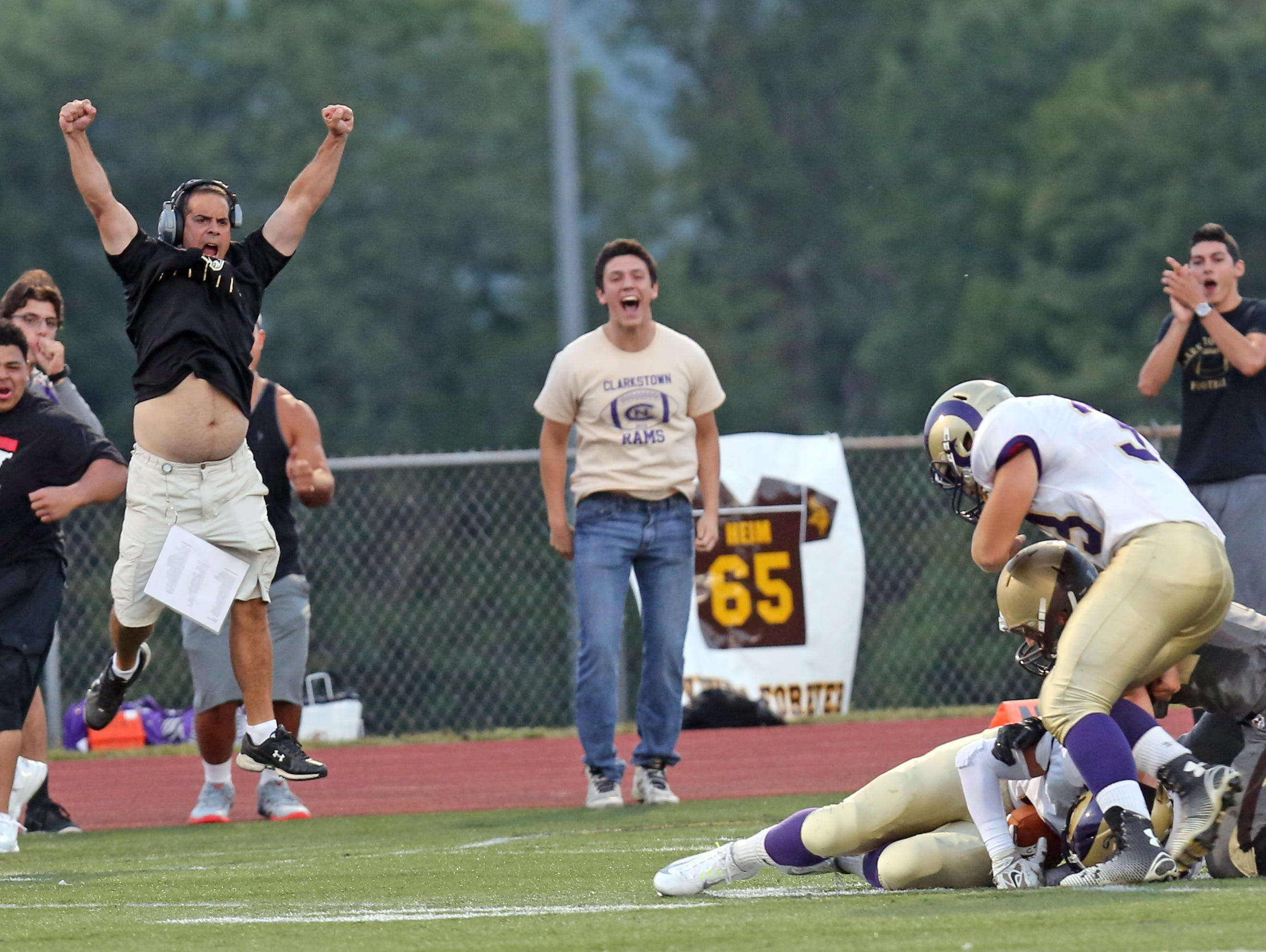 Clarkstown North's side line celebrates when Rhys Farrell-Bryan (7) intercepts the ball from Clarkstown South's Kyle Samuels (4) during game action at Clarkstown South High School in West Nyack Sept. 4, 2015. Clarkstown North defeated Clarkstown South 26-8.