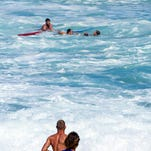 Bodyboarder Andre Botha, top left, watches as two lifeguards help him rescue pro surfer Evan Geiselman, second from right, as surfer Mick Fanning, bottom center, runs toward the ocean at the North Shore Oahu surfing spot known as Pipeline, near Haleiwa, Hawaii, on Dec. 6.