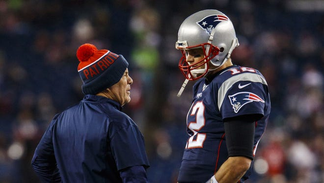 New England Patriots quarterback Tom Brady (12) talks with head coach Bill Belichick before the start of the game against the Seattle Seahawks at Gillette Stadium.