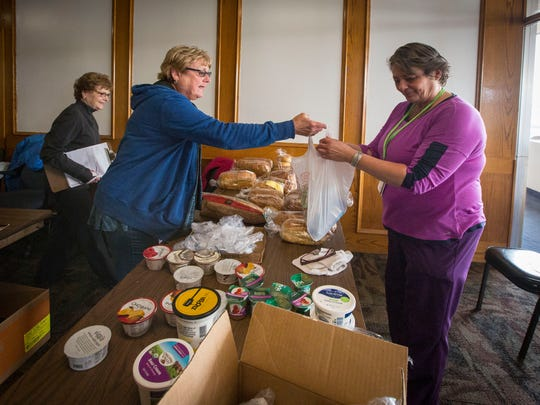 Christine McManus, 48, right, works for minimum wage cleaning rooms at the Motel 6 in Clinton. During her lunch break on Wednesday March 9, 2017, she and many of the maids take a free sack lunch given by the Franciscan Peace Center.
