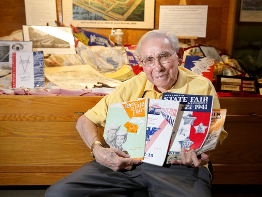 Wisconsin State Fair Historian Jerry Zimmerman holds an assortment of past Wisconsin State Fair programs as he sits in front of a display of Wisconsin State Fair historic memorabilia inside the Exploratory Park at State Fair Park in West Allis.