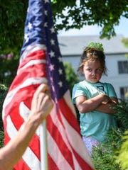 "Chloe Ashby, 5, of Evansville, Ind., finds a shady spot to cool off as her grandmother Debbie Emge of Wadesville, Ind., props up an American Flag during the 'Families Belong Together' rally outside of the Winfield K. Denton Federal Building, which houses a Dept. of Homeland Security office, in downtown Evansville, Ind., Saturday, June 30, 2018. Ashby's mother, Allison Ashby, brought her to the protest to ""teach her that we [as American citizens] are allowed to protest and we don't have to agree with everything that goes on."""
