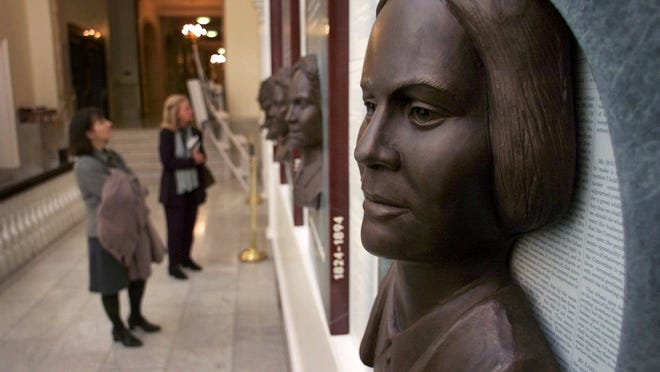 "Guests view a work of art titled ""Hear Us,"" featuring six bronze reliefs highlighting the contributions of women in public life in Massachusetts at the Statehouse in Boston. In the foreground is the likeness Lucy Stone, an editor and suffragist in the 1800s."