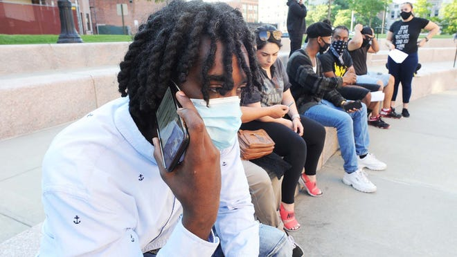 Ariff McLaren listens to the budget meeting on his phone during a peaceful gathering outside Brockton City Hall on Wednesday, June 24, 2020, calling for the defunding of the Brockton Police Department.