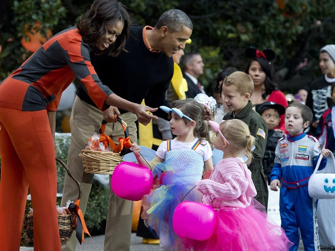 First lady Michelle Obama and President Obama hand out treats to children as they arrive for a Halloween event on Oct. 31 on the South Lawn of the White House in Washington.
