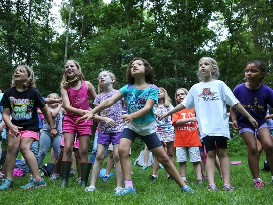 Campers swing their arms while learning a song during