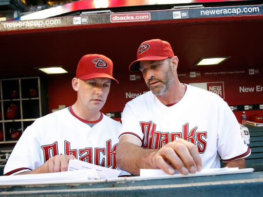 158664 Dbacks0508 - August 5, 2009 - Coach Kirk Gibson reviewed the record with the new Arizona Diamondbacks captain AJ Hinch before he managed his first match against the Washington Nationals at Chase Field in Phoenix, AZ.  Hinch replaces the fired Bob Melvin.