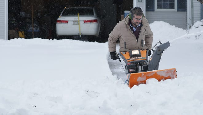 Steve Nesmith tries to clear a path for his vehicle Monday morning in Appleton after a snowstorm left his driveway buried in snow.