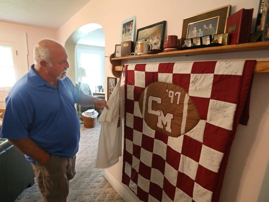 Former Caledonia-Mumford head football coach Mike Monacelli, who was proactive in researching head injuries in high school sports, looks over a quilt honoring the 1997 Cal-Mum team as he talks about the current state of football from his living room in Caledonia  Wednesday, Aug. 1, 2018.