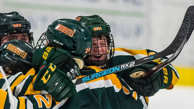 Teammates congratulate St. Albans #24 Parker Gratton after his goal pulled the Bobwhites ahead 2-1 during their boy's hockey game Wednesday night, Jan 3, 2018, at Essex.