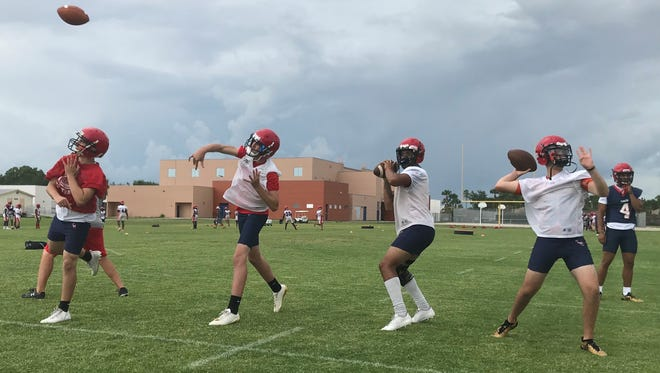 St. Lucie West Centennial quarterbacks (from left) Enrique Crespo, Lance Bianchini, Myles Youngblood and Ashton Houser throw during the first day of spring practice Monday, April 23, 2018, at Centennial.