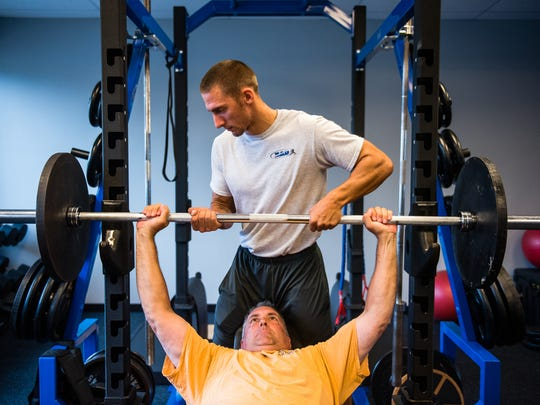 Personal trainer Kyle Aumen helps client Andrew Smith with weight training Thursday morning June 16, 2016 at the Institute for Athletic Development on Eisenhower Drive.