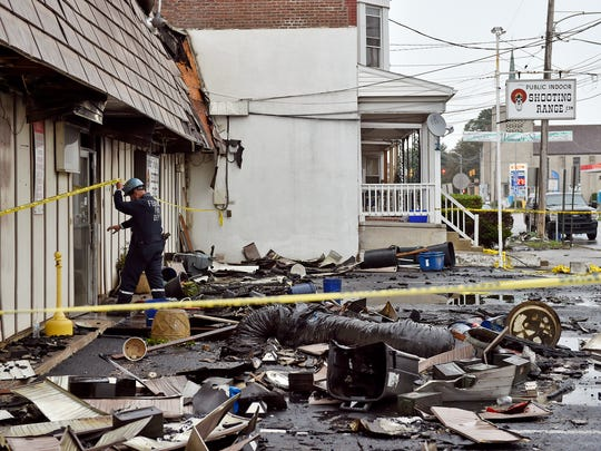 A federal law enforcement officer enters the West York Sporting Good store Saturday, about 12 hours after a three-alarm fire destroyed the public indoor shooting range.
