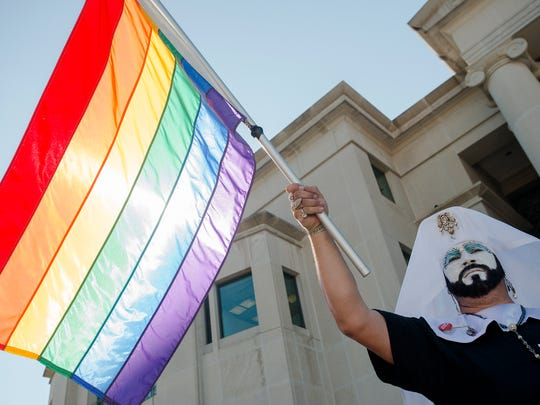 Robert Dodge holds a rainbow flag during the ethics
