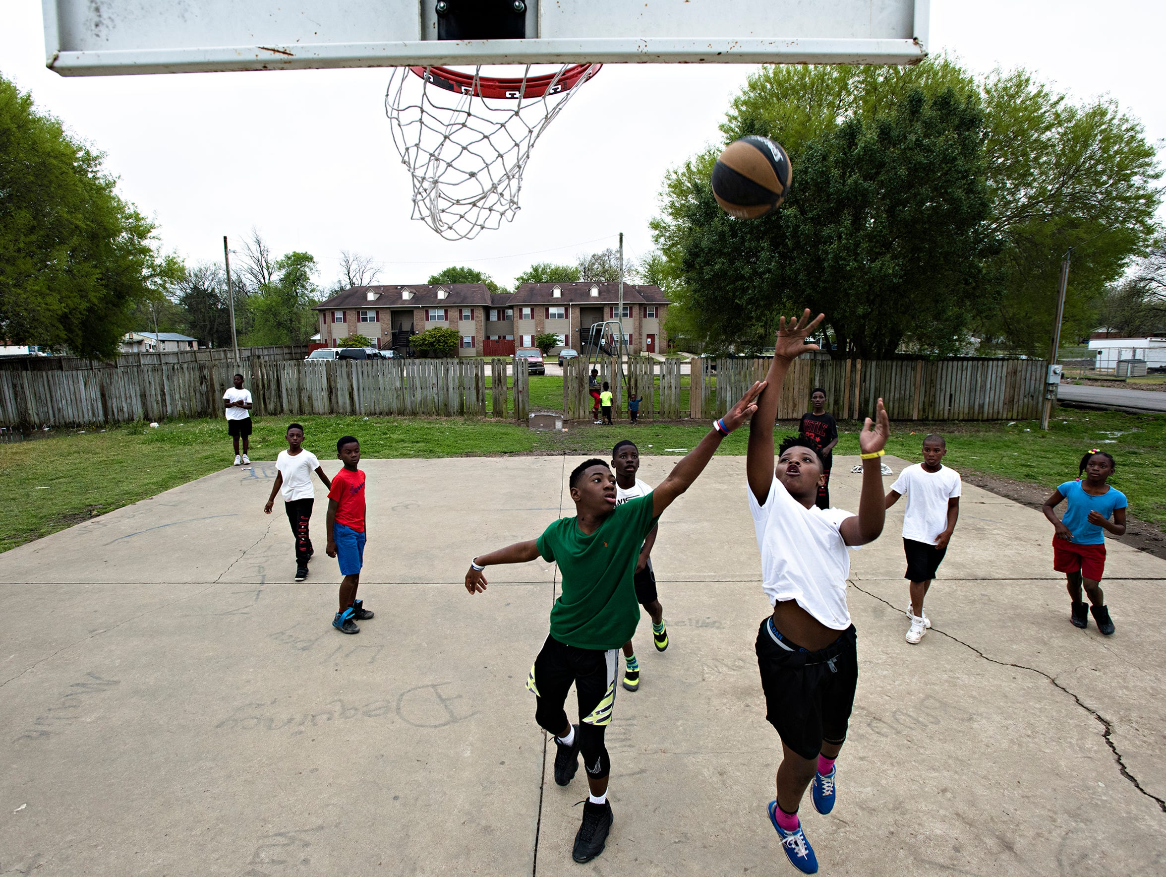 Children play basketball on a court near public housing