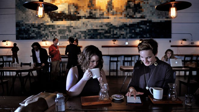 Visiting Canadians Jessica Knapp, left, and Tamar Cachet enjoy coffee at Barista Parlor. The coffee shop has been in The Shops at Gallatin & Stratton building for three years.