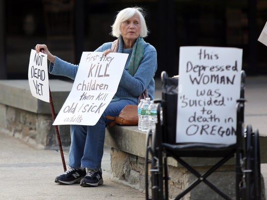Caroline Hass, 84, holds up signs as people gathered
