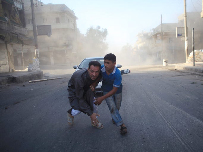 Syrian men react during an airstrike reportedly by government forces July 15 in the northern city of Aleppo. More than 170,000 people have been killed in the three-year Syrian war, one third of them civilians, according to the Syrian Observatory for Human Rights.