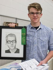 Spencer Dofflemyer, of James Buchanan Senior High, holds up his self portrait, for which he won the Ralph Snider Scholarship Award as part of the The Franklin County Art Alliance's 45th annual exhibition.