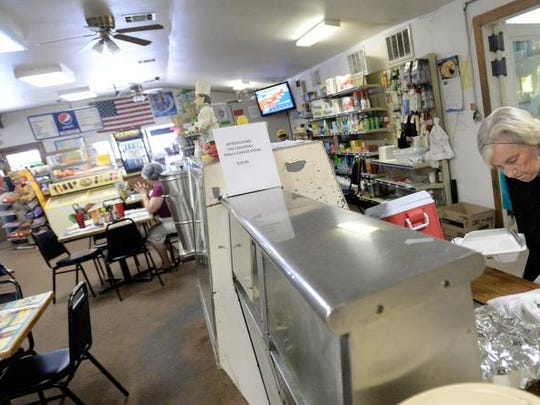 Charlotte Sandlin dishes out an order behind the counter at Longwood General Store.