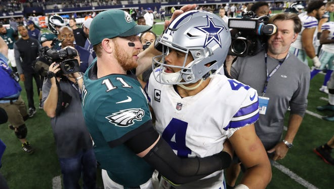Philadelphia Eagles quarterback Carson Wentz (11) meets with Dallas Cowboys quarterback Dak Prescott (4) after the game at AT&T Stadium.