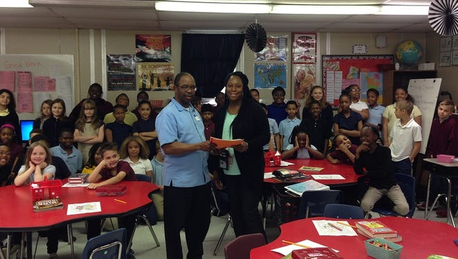 This submitted photo shows Princess Anne Elementary School 2016 Teacher of the Year Toni Stewart-Brown, receiving a certificate of appreciation from Princess Anne Town Commission President Garland Hayward, as students in her class look on. Stewart-Brown and 11 students attended a recent meeting of town officials to discuss the value of carbon monoxide detectors in homes. Stewart-Brown also led a student drive that raised funds toward the purchase of CO detectors for homes.
