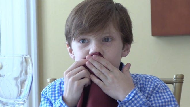 Child wipes mouth with napkin at dinner table
