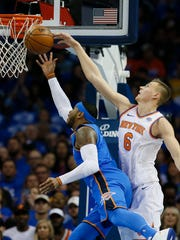 New York Knicks forward Kristaps Porzingis (6) blocks a shot by Oklahoma City Thunder forward Carmelo Anthony, left, in the first quarter of an NBA basketball game in Oklahoma City, Thursday, Oct. 19, 2017.
